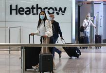 Passengers, wearing protective face masks, walk through the international arrivals hall after arriving at Heathrow Airport in London