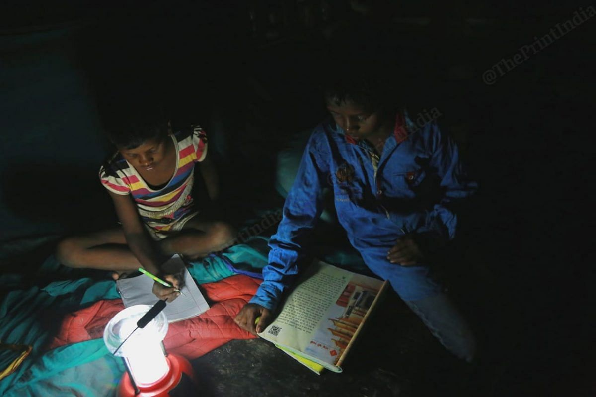 Children in the village use a night lamp to study. The night lamp is charged using a solar plate provided by a NGO| Photo: Manisha Mondal | ThePrint