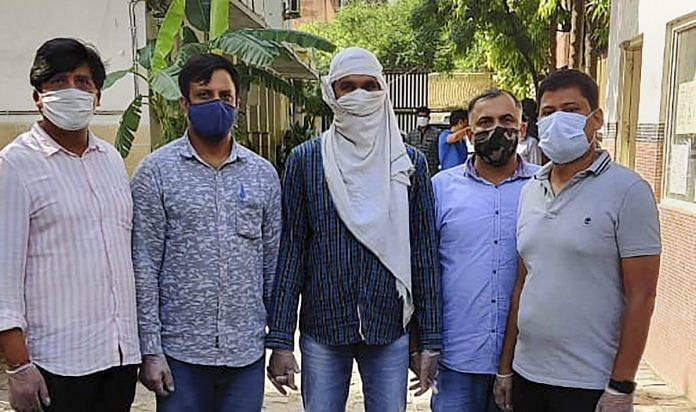 Delhi Police with an alleged ISIS operative (Centre) after arresting him last night from central Delhi's Ridge Road area on 22 August | PTI Photo