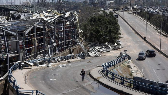 A pedestrian walks along a road past destroyed commercial warehouse buildings in Beirut, Lebano | Photographer: Hasan Shaaban | Bloomberg