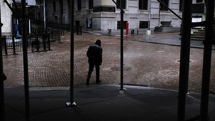 People walk along Wall Street as the coronavirus keeps financial markets and businesses mostly closed in May, 2020 in New York City. | Photo: Spencer Platt | Bloomberg via Getty Images