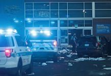 A Police officers inspect a damaged Best Buy store after parts of the city had widespread looting and vandalism, on August 10, 2020 in Chicago. | Bloomberg