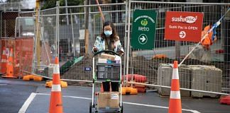 A pedestrian wearing a protective mask pushes a cart in Auckland, New Zealand due to Covid lockdown   Brendon O'Hagan/Bloomberg