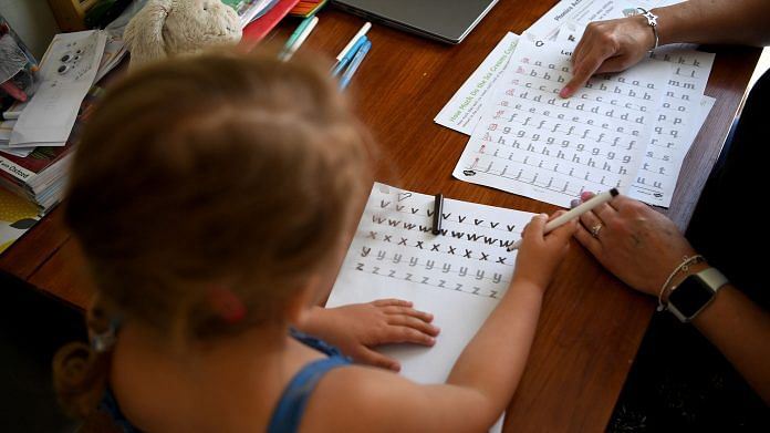A girl studying at home with her mother (Representational Image) | Photo by Gareth Copley | Getty Images via Bloomberg