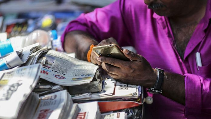 A vendor uses a smartphone while waiting for customers at a newspaper stand in Mumbai, India | Photographer: Dhiraj Singh | Bloomberg
