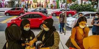 Shoppers use hand sanitizer as a vendor checks a customer's temperature outside a store during a partial lockdown imposed due to the coronavirus in Kuala Lumpur, Malaysia | Bloomberg