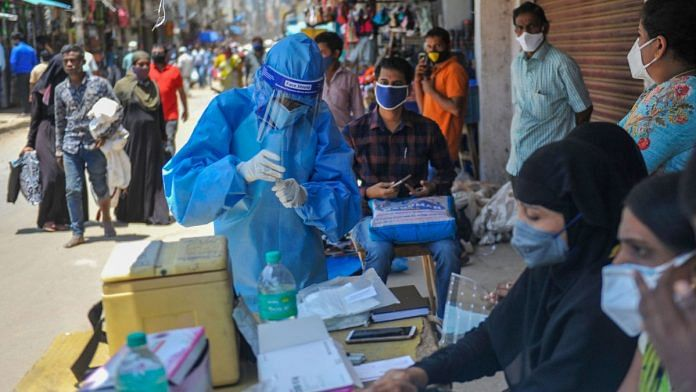 A medic in PPE collects samples for Covid-19 tests in Bengaluru on 25 August 2020 | PTI