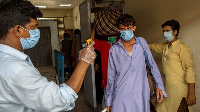 A passenger wearing a mask has his temperature checked at Karachi Cantonment railway station, in Karachi, Pakistan, on Tuesday, July 28, 2028 July 2020 Asim Hafeez | Bloomberg