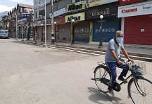 A man cycles past closed shops on a deserted road amid curfew in Srinagar Tuesday   Azaan Javaid   ThePrint