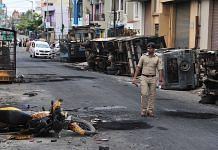 Representational image. | A police personnel marches in Devara Jeevana Halli, where an angry mob attacked and vandalised properties, in Bengaluru. | Photo: ANI