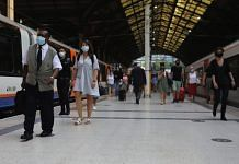Commuters wearing protective face masks walk along a platform at Liverpool Street railway station, in London on 12 August