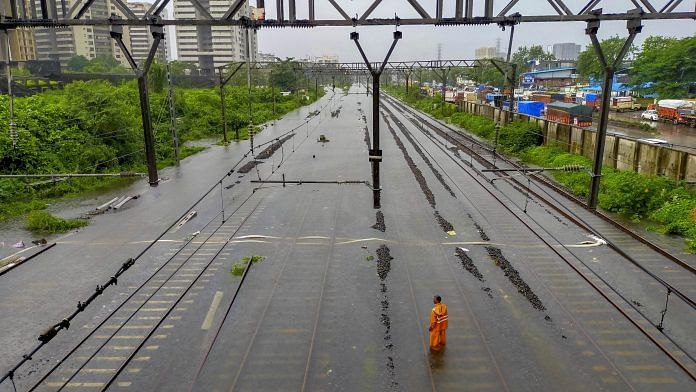 A man stands on waterlogged railway tracks between Kurla and Sion, following heavy rainfall, in Mumbai | PTI