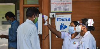 A staff nurse uses a thermal screening device on an employee at a hospital | PTI