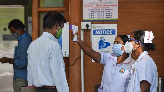 A staff nurse uses a thermal screening device on an employee at a hospital   PTI