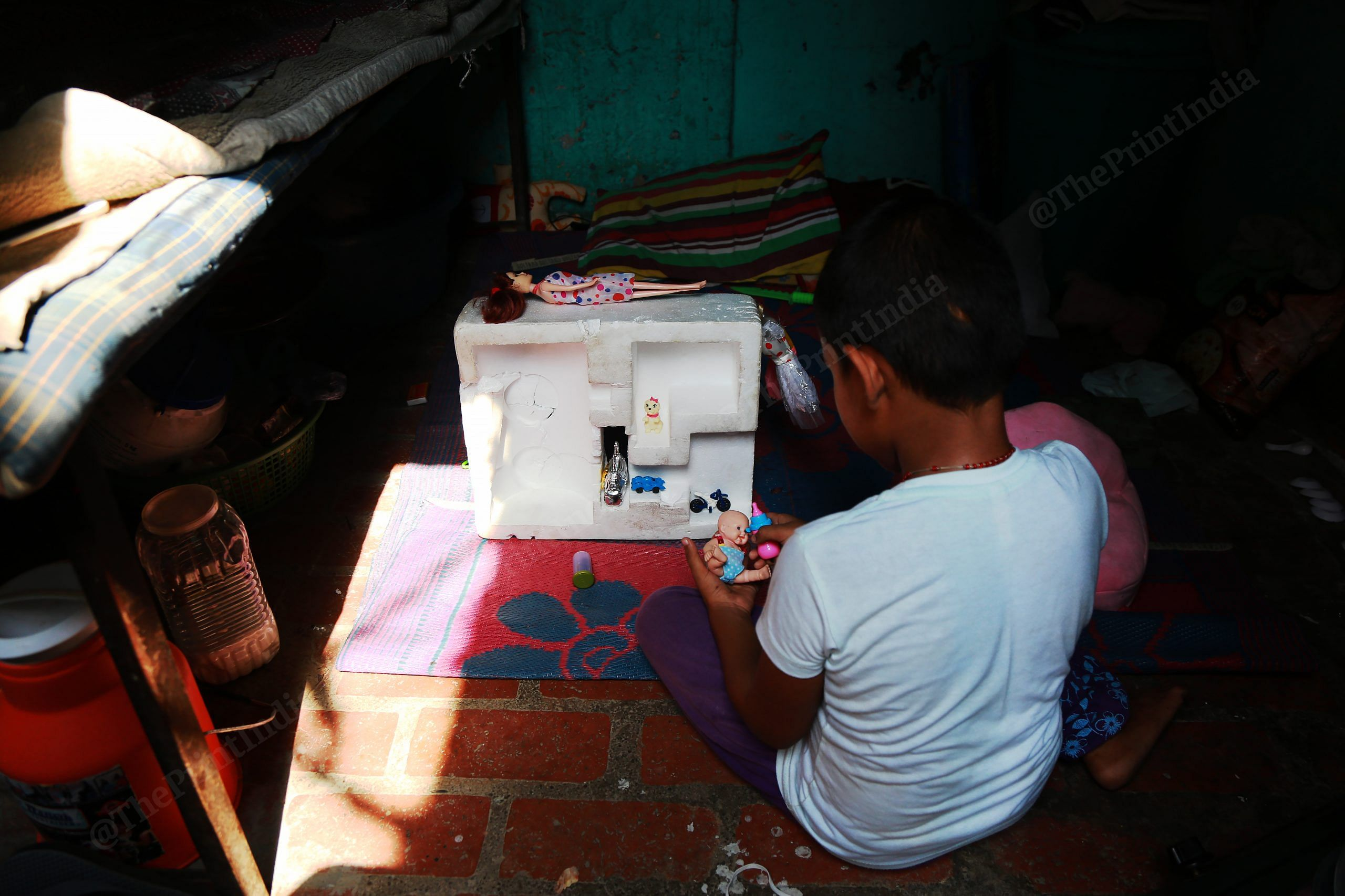 A sex worker's child plays with a dollhouse she has fashioned out of a thermocol box | Manisha Mondal | ThePrint
