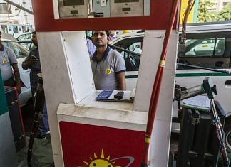 An employee refuels a vehicle with compressed natural gas (CNG) at an Indraprastha Gas Ltd. gas station in New Delhi | Photographer: Prashanth Vishwanathan | Bloomberg