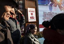 """A sign warning against """"uncivilized behavior"""" is displayed as spectators watch a street performance in the main bazaar in Urumqi, Xinjiang autonomousregion, China 