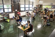 Students wearing protective masks work at their desks at a school in US | Photographer: Daniel Acker | Bloomberg