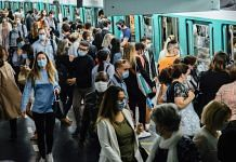 Morning rush hour commuters wear protective face masks while boarding and exiting a train at Saint-Lazare metro railway station in Paris, France. | Photographer: Cyril Marcilhacy | Bloomberg