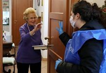 A volunteer from the Community of Sant'Egidio, speaks to an elderly woman during a home-care service during lockdown in in Rome, Italy | Photo by Marco Di Lauro | Getty Images via Bloomberg