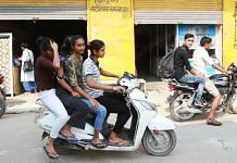 People ride triples on a scooter in Dabua colony, a containment zone in Faridabad, on 10 September 2020 | Manisha Mondal | ThePrint