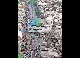 A mosque in the middle of the road located in a crowded area from Madhya Pradesh