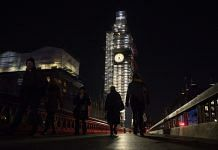 Pedestrians in front of the Elizabeth Tower at the Houses of Parliament at night in London