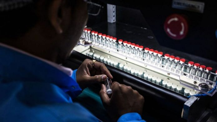 A technician inspects vaccine vials for defects during a screening process at the Serum Institute of India Ltd. pharmaceutical plant in Pune in 2015. | Photographer: Sanjit Das | Bloomberg