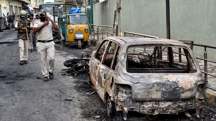 Police personnel pass by vehicles burnt by a mob in Bengaluru on August 12