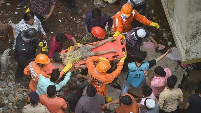 National Disaster Response Force NDRF and Fire brigade rescue an injured child after a three storey building collapsed, at Bhiwandi in Thane district, Monday | PTI