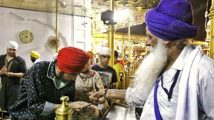 A sewadar gives prasad to a devotee at Golden Temple. None of them is wearing a mask. | Photo: Praveen Jain/ThePrint