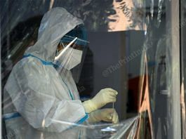 A health care worker in a PPE suit with a sample in a vial