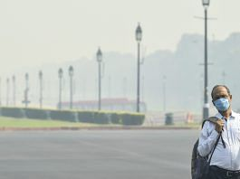 A man wearing a face mask walks on Rajpath road amid hazy weather conditions in October 2020 | PTI