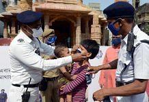 Kolkata Police personnel make a child wear a mask outside a Durga Puja pandal Tuesday | Photo: ANI