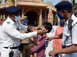 Kolkata Police personnel make a child wear a mask outside a Durga Puja pandal Tuesday   Photo: ANI