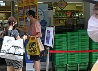 People waiting to enter a supermarket have their identity documents checked by staff in Singapore (Representational image) | Photo: Roslan Rahman | Getty Images/AFP via Bloomberg