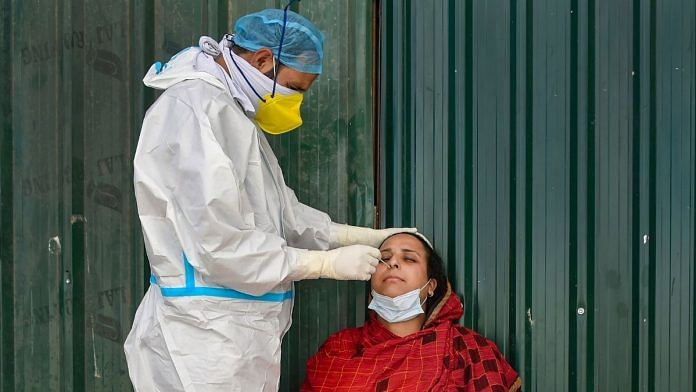 A health worker wearing PPE kit collects sample from a woman for COVID-19 test, at Chanpora, in Srinagar, Thursday, Oct. 1, 2020 | Representational image | PTI