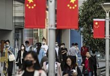 Morning commuters wearing protective masks walk past Chinese flags displayed along Nanjing Road in Shanghai, China | Representational image | Qilai Shen | Bloomberg