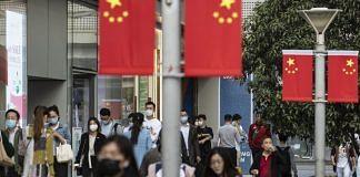 Morning commuters wearing protective masks walk past Chinese flags displayed along Nanjing Road in Shanghai, China | Representational image | Qilai Shen | Bloomberg