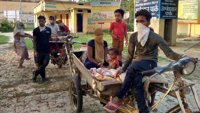 Kaushal Kumar (in front) and Ranjit Kumar with their families on the rickshaw carts that brought them home (Photograph taken in May) | By special arrangement
