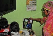 A family member of Nikita Tomar holds her picture at her home. | Photo: Suraj Singh Bisht/ThePrint