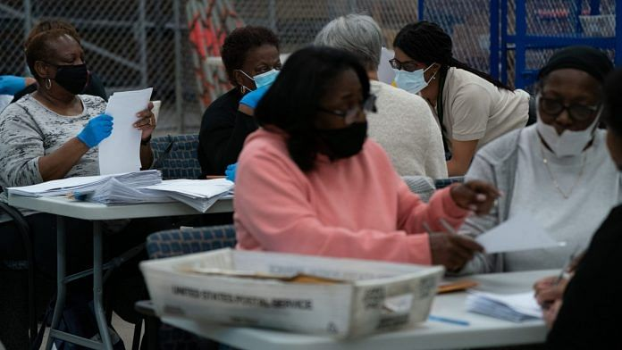 Election officials wearing protective masks count military absentee ballots for the 2020 Presidential election in Georgia, US, on Thursday, Nov. 5, 2020. | Photographer: Elijah Nouvelage | Bloomberg
