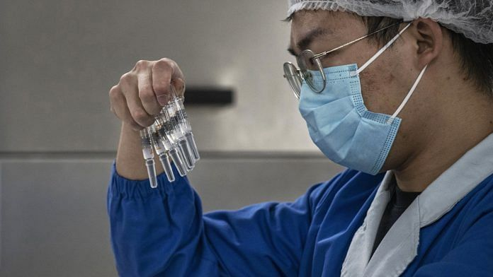 A worker checks syringes of a potential vaccine Corona Vac on the production line at Sinovac Biotech in Beijing on 24 September