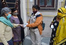 Volunteers use an oximeter to measure the oxygen level during a door-to-door campaign to check symptomatic Covid-19 residents, amid rise in coronavirus cases, in East Delhi, on 22 Nov., 2020. | PTI