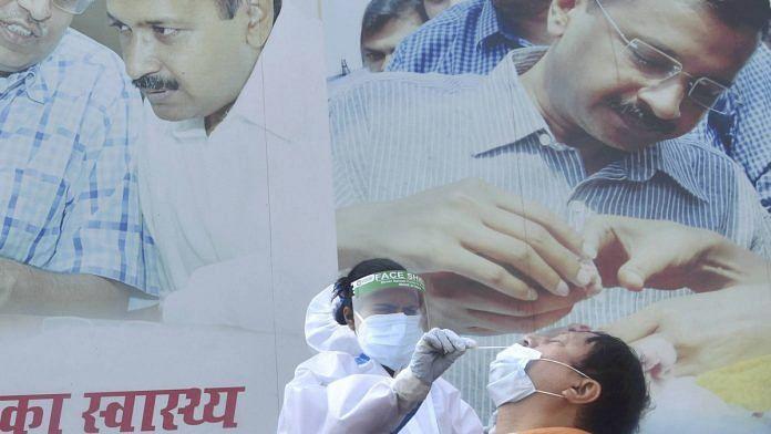 A health worker conducts Covid test outside a mohalla clinic in Delhi, 20 Nov 2020   PTI