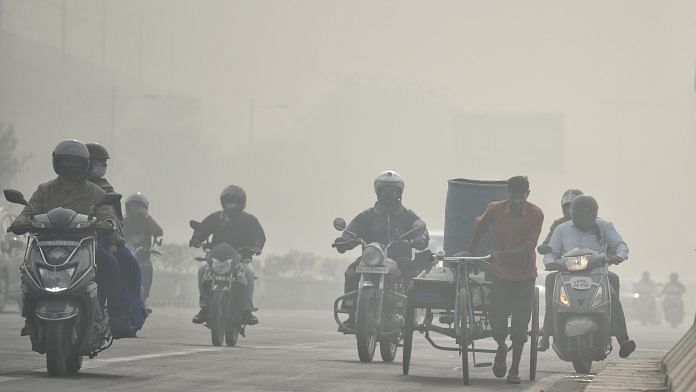 Commuters on two-wheelers plying through a thick layer of smog in New Delhi on 10 November   ANI Photo