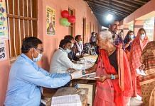 An election officer applies indelible ink on the finger of an elder voter at a polling station in Vaishali on 7 November