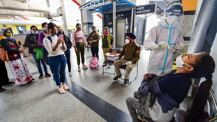 A health worker in protective gear collects a swab sample from a passenger at Nizamuddin Railway Station in New Delhi, on 25 November 2020 | PTI
