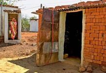 A woman walks out of a village toilet | Commons