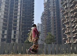 File image of a woman walking past buildings under construction in Noida, Uttar Pradesh | Photo: Anindito Mukherjee/Bloomberg